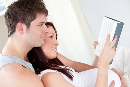 Close-up of a pregnant woman and her husband reading a book on t