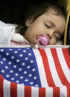 A baby sleeps with an American flag at a