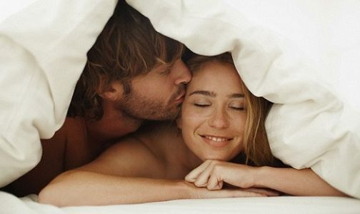 Young couple snuggling under a blanket